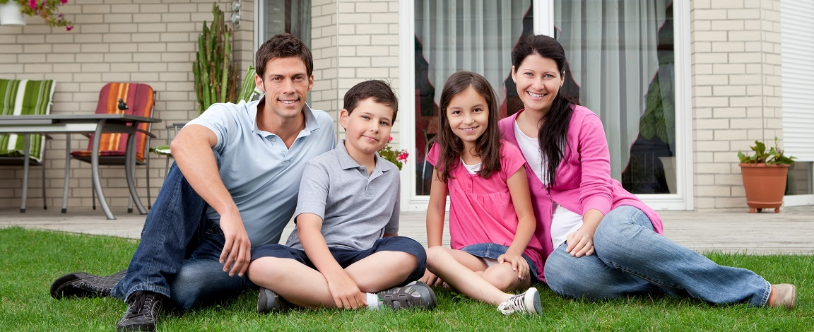Portrait of happy family of four sitting in backyard of new home